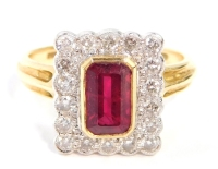 An 18ct gold ruby and diamond dress ring, with rectangular cut, central ruby in rub over yellow gold setting, surrounded by tiny diamonds, pave set in white gold on a raised and pierced shank, with two ribbed shoulders, ring size K½, 5.2g.