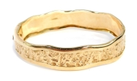 A 9ct gold waved and hammered hinged bangle, the wave design outer thick border with central hammered panel, 6cm diameter, 42.1g all.