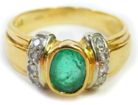 An emerald and diamond dress ring, the oval emerald in a rub over setting with tiny diamond set shoulders set in white metal, on a three channeled band, yellow metal stamped 750, ring size M½, 5.1g all in.