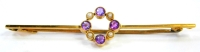 An Edwardian bar brooch, with central circular design set with four seed pearls and four amethysts, on a yellow metal bar with copper pin, the bar stamped 15ct, 5.5cm wide, 2.2g all in.