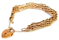A 9ct rose gold gate bracelet, of multi curb link design, with outer elongated bent in borders, with a 9ct gold heart shaped padlock clasp, and safety chain, the bracelet 19cm long, 27.4g.