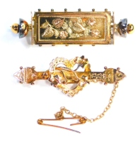 Two bar brooches, comprising a 9ct gold Edwardian bar brooch, with central heart and leaf decoration, 4cm wide, and another 9ct gold example, with rectangular floral central bar and two bobbin ends, 4.5cm wide, 7.2g all in.