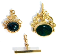 Two swivel agate fobs and a bar brooch, comprising a 9ct gold swivel agate pendant, with green and cream/brown swivel agate on heavily scrolled design top, 4cm high, 3cm wide, a further smaller example in 9ct set with cabochon tigers eye and red and green