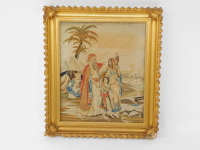 An early 19thC petit point picture, depicting figures and animals in a desert, gilt framed, 52.5cm high, 43.5cm wide.