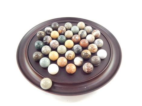 A polished treen solitaire board, with marble polished piece of large form, the board 33cm diameter.