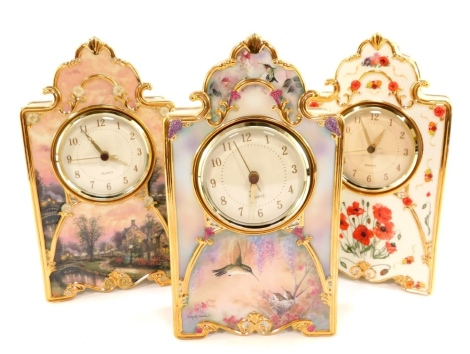 A Bradex Heirloom porcelain clock In Flanders Field, limited edition, A1776, a mantel clock Garden Whispers, by Larry Martin, limited edition A8152, and Lamp Light Lane Heirloom porcelain clock by Thomas Kinkade, A5490, 23cm high. (3)