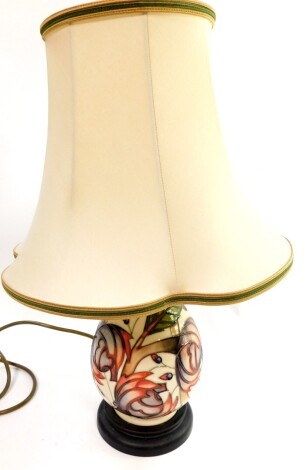 A Moorcroft pottery table lamp decorated with flowers, against a cream ground, of baluster form with shade, 45cm high.