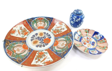 A Japanese Imari charger, decorated with birds and flowers, 40cm diameter, together with a Chinese fluted dish and a blue and white ginger jar and cover decorated with prunus blossom against a cracked ice ground. (4)