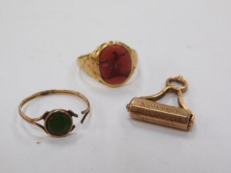 A carnelian crested signet ring, set in yellow metal, size K, further ring, and a roller seal, with engraved named detailing, yellow metal, 6.5g all in.