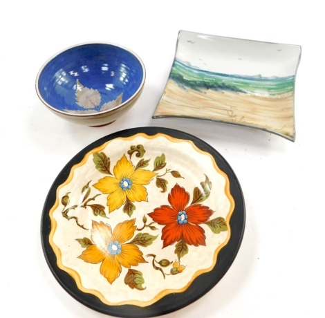 A Highland stoneware pottery dish, painted with a coastal scene, 18cm wide, a Gouda pottery plate decorated in the Anita pattern, and an Island of Syke pottery bowl decorated with a leaf against a blue ground. (3)