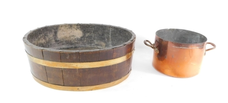 A late 19thC coopered oak wine cooler, of oval form, with brass banding and a lead lining, 23cm high, 69cm wide, 54cm deep, and a late Victorian copper pan of large proportion circular form, with fixed handles marked R3. (2)