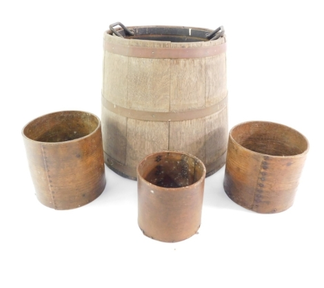 A early 20thC oak coopered barrel, of tapering circular form with metal banding, 40cm high, various other treen, barrels, circular grain measures, etc. (a quantity)