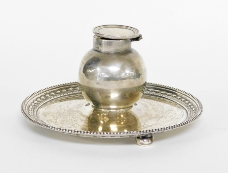 An Edward VII silver inkwell and stand, the bulbous shaped inkwell on a circular tray base, with fluted and ribbed borders, on three bun feet, makers stamp JD&S, Birmingham 1904 (AF), 7cm high, 13cm wide, 6½oz gross.