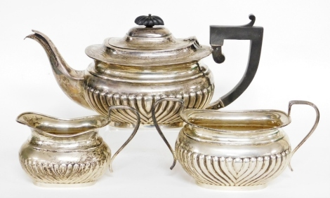 A George V silver three piece tea service, comprising teapot, milk jug, sugar bowl, the teapot with ebonised handle and knop, on a fluted body, Birmingham 1928, 39½oz gross.