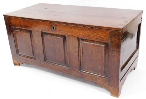 A late 17thC oak coffer, with three panelled front with brass escutcheon, 56cm high, 117cm wide, 54cm deep.