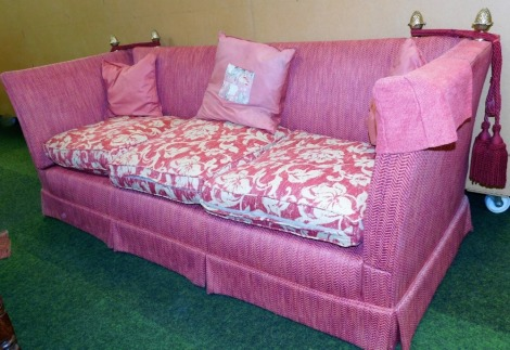 A Knole style three seater sofa, in a red upholstery, with brass acorn finials and ties, 80cm high, 225cm wide, 83cm deep.