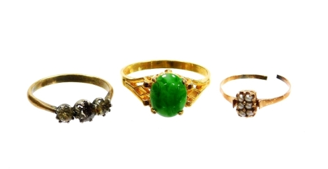 Three dress rings, to include a gold and seed pearl set dress ring, cut yellow metal unmarked, 0.7g, a silver and paste stone set three stone dress ring and a jade set dress ring, on a 18ct gold plated band. (3)