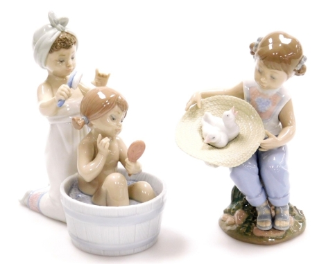 Two Lladro figure groups, to include a girl having a bath, with figure brushing hair no. 6457, 17cm high, and a figure of a girl with hat with two doves no. 6759, 17cm high (2).