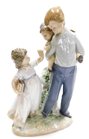A Lladro figure group, of friends and family, with a boy having a piggyback, and girl with reading books no. 5702, 26cm high.