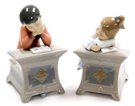 Two Nao porcelain figures, of children at desk, reading and writing, boy and girl, no.1403 and 1494, 16cm high (2).