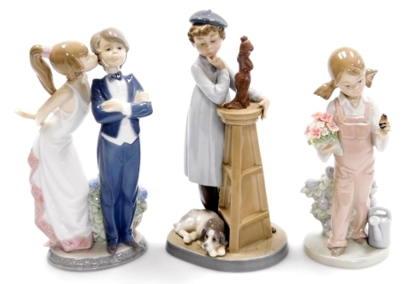 Three Lladro figures, to include a Bride and Groom no. 5555, 22cm high, a figure of a female and dog with sculpture, no. 5358, 21cm high, and another of a girl carrying a basket with bird no. 5217, 19cm high (3).