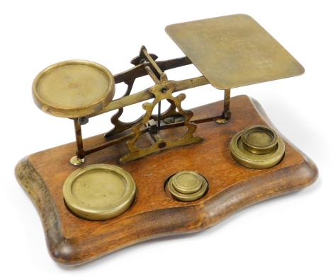 A set of early 20thC brass postal scales, on a wooden base with inscription postage rates for letters with an assortment of five weights on shaped mahogany base, 15cm high, 26cm wide, 14cm deep.