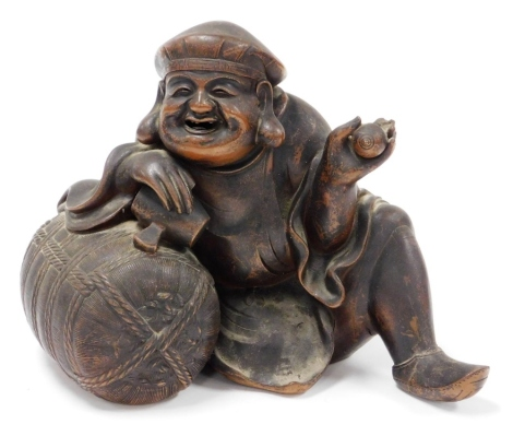 A Chinese terracotta figure of a seated man, 24cm high, 26cm wide.