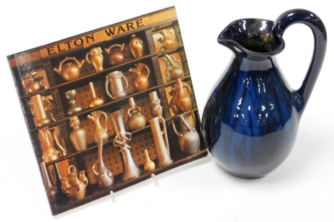 An Eltonware pottery jug, circa 1900, in a blue glazed decoration with Eltonware information book, 26cm high. (2)