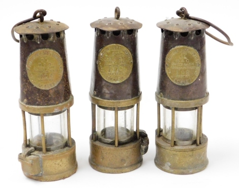Three Miner's lamps, each for Eccles numbered 104, 131, and 196, one lacking carry hook, 25cm high. (3)