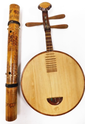 Two wooden instruments, to include a Valiha and a Yuegin Chinese moon guitar.