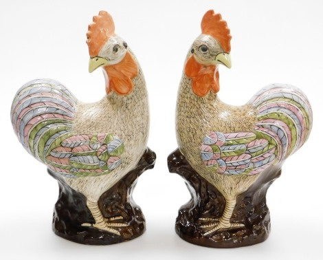 A pair of late 20thC Chinese pottery figure of cockerels, with enamelled decoration, 49cm high.
