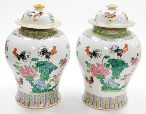 A pair of Chinese porcelain baluster vases and domed covers, decorated with cockerels and peonies between lappet and key fret borders, 20thC, 40cm high.