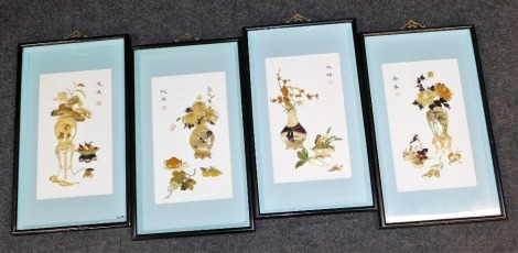 A set of four Chinese mother of pearl pictures, each depicting vase of flowers with applied relief mother of pearl, with a blue border and black ebonised surround, 42cm x 21cm. (4)