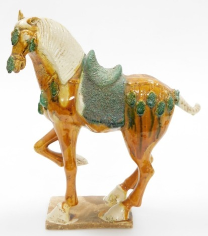 A Chinese terracotta horse in Tang style, decorated in green and orange glaze on a rectangular base, 40cm high.