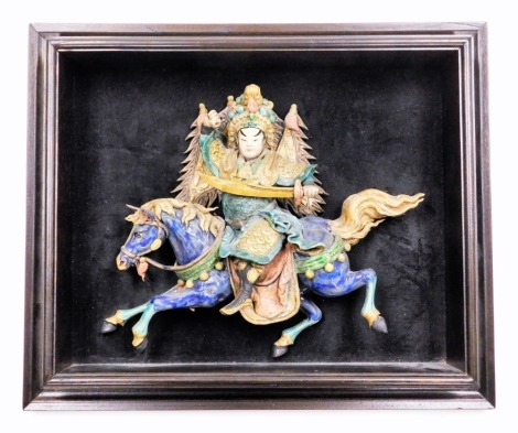 A Chinese framed pottery figure of a GeneralYu Kao from the Peking Opera, on horseback decorated in bright colours on a black background, 53cm x 43cm.