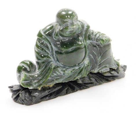 A Chinese carved green hardstone figure of a seated Putai, carved wood stand, 10cm high, 14cm wide.