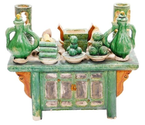 A Chinese Tang style sancai pottery model of a cabinet, festooned with food and pottery vessels in traditional colours of green , brown and olive glazes, probably of the period, 24.5cm high, 28cm wide.
