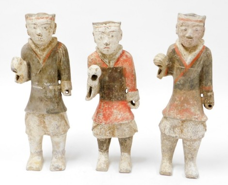 A set of three Western Tang Dynasty painted pottery figures of warriors, each figure standing in holding postures, probably Xiang, Shaanxi Province, 49cm - 53cm high.
