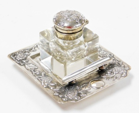 A Chinese silver ink stand, the cut crystal well having a repoussé decorated cover, the square stepped base with floral decoration pen rest, makers mark 'YOK SANG' to base, 11cm square. Yok Sang is thought to have been based in Shanghai and was active at