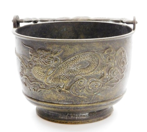 A Japanese bronze brazier with swing handle, low relief decoration of dragons among clouds, 30cm high.