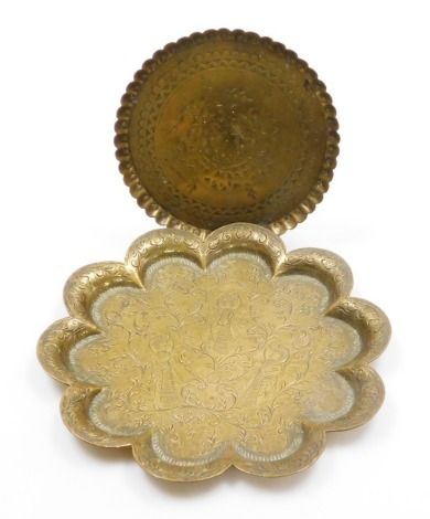 Two Eastern brass trays, to include a circular tray with central medallion, 17cm wide, and a scalloped dish, with scrolling flowers and holy figures, 25cm wide. (2)
