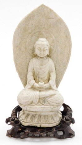 A Chinese carved limestone figure of Buddha seated on a lotus base, holding a cup, the mandala with etched flame designs, on a carved pierced wood base, 18thC or earlier, 44cm high, 24cm wide, 16cm deep.