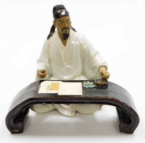 """A Chinese terracotta and white glazed """"mudman"""" figure of a scholar seated at table, the gentleman AF, 27cm high, with a painted table with applied inkstone, brush rest and various papers, 9cm high, 27cm wide."""