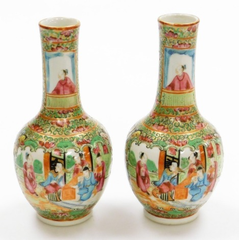 A pair of 19thC Chinese Canton porcelain bottle vases, with panels of figures at court, birds and butterflies, within gilt and painted bands, 19cm high.