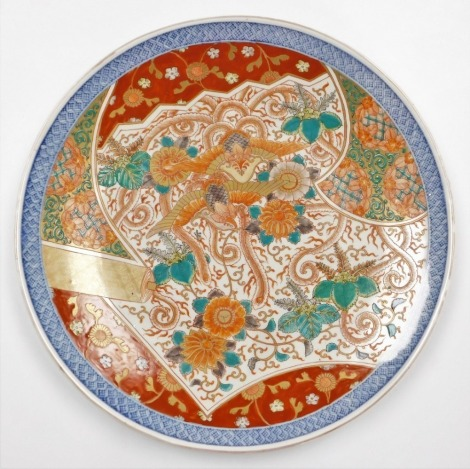 A Japanese Imari charger, decorated with a central design of phoenic and chrysanthemums within a shaped panel, underglaze blue diaper border, the reverse with tasselled cash in blue, Meiji period, 46cm diameter.