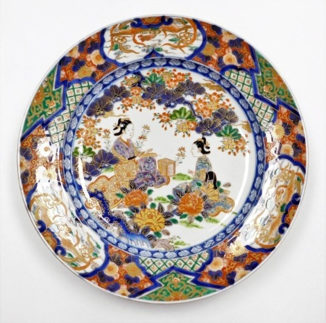 A Japanese porcelain Imari charger, decorated with a central panel of seated woman in garden, winin a wide border of phoenix, chrysanthemums and diaper patterns, the reverse with floral sprays, Meiji period, 40cm diameter.