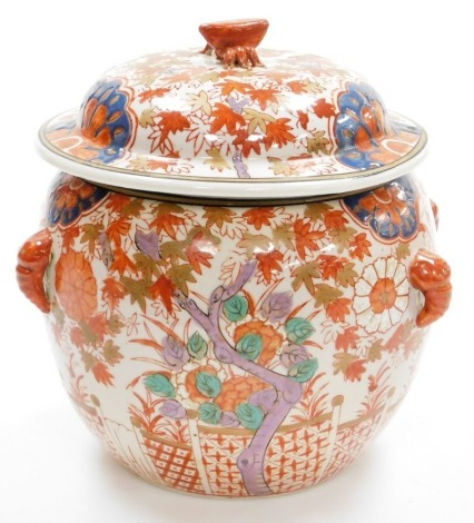 A 20thC Japanese Imari tureen and cover, decorated with trees beside fences, chrysanthemums, four elephant head handles, signed on the base, Meiji/Taisho period, 22cm high.
