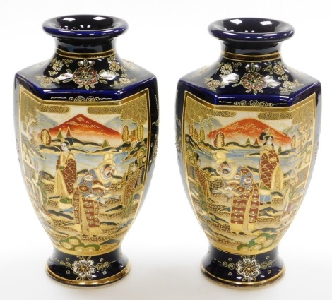 A pair of 20th Japanese Satsuma hexagonal baluster vases, decorated with panels of deities beneath Mount Fuji, signed to base, 24cm high.
