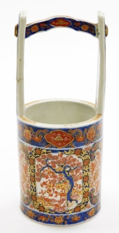 A 19thC Japanese Imari porcelain vase shaped as a well bucket, decorated with panels of trees, scrolls and shishi, signed to base, Meiji period, 30cm high. (AF)