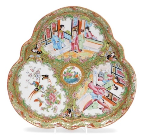 A 19thC Chinese Canton porcelain trefoil dish, decorated with three panels of court scenes and floral design, 27cm diameter.